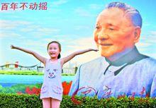 一个可爱的女孩在邓小平画像前留影